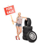 Woman holding a for sale sign by a pile of tires Stock Photos