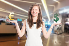 Woman holding and scaling euro and dollar sign. With fade mall background royalty free stock images