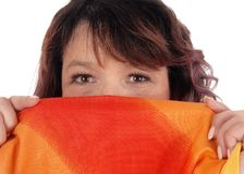 Woman holding scarf over mouths. A brunette woman holding a colorful scarf over her mouths, looking Royalty Free Stock Image