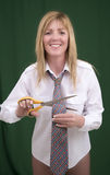 Woman holding scissors to cut through a necktie Stock Image