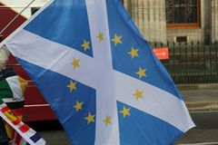 Woman Holding a Scottish Flag with EU Flag Stars in Edinburgh stock photo