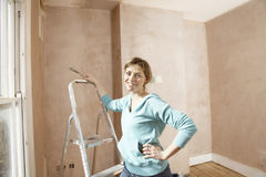 Woman Holding Scraping Tool In Unrenovated Room Royalty Free Stock Image