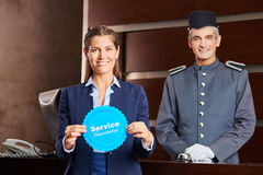 Woman holding service guarantee sign in hotel. With smiling concierge behind her Stock Image