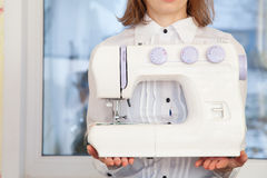 Woman holding sewing machine Royalty Free Stock Image