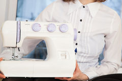 Woman holding sewing machine Royalty Free Stock Photos