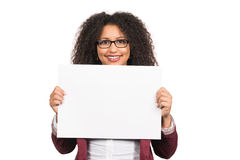 Woman is holding a sheet of paper. Cut out image of a young woman with brown curly hair (afro) and glasses who is holding a white empty sheet of paper Royalty Free Stock Images