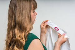Woman holding a shirt with lipstick of her unfaithful husband Royalty Free Stock Image