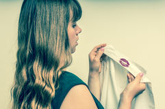 Woman holding a shirt with lipstick of her unfaithful husband Stock Image