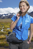Woman Holding Shoes By Mountain Pond Stock Image