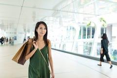 Woman holding shopping bag ans walking along the street Royalty Free Stock Photos