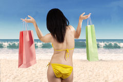 Woman holding shopping bag at beach Stock Photos