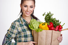 Woman holding a shopping bag full of fresh food Royalty Free Stock Images
