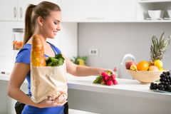 Woman holding a shopping bag full of fresh food Royalty Free Stock Photos