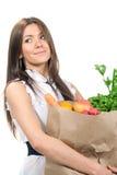 Woman holding a shopping bag full of groceries. Happy young woman holding a shopping bag full of groceries, mango, salad, asparagus, radish, avocado, lemon Stock Photo