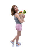 Woman holding a shopping bag full of groceries. Back view portrait of a smiling woman holding a shopping bag full of groceries Stock Photos
