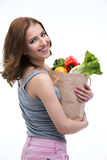 Woman holding a shopping bag full of groceries. Happy beautiful woman holding a shopping bag full of groceries Royalty Free Stock Photography
