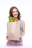 Woman holding a shopping bag full of groceries. Happy woman holding a shopping bag full of groceries and looking on at camera Royalty Free Stock Image