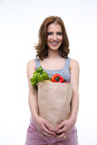 Woman holding a shopping bag full of groceries. Smiling cute woman holding a shopping bag full of groceries Royalty Free Stock Photography
