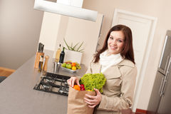 Woman holding shopping bag with grocery in kitchen Royalty Free Stock Photos