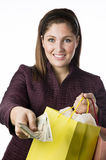 Woman holding shopping bag passing money Royalty Free Stock Photos