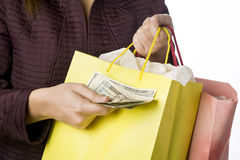 Woman holding shopping bag passing money Stock Photo