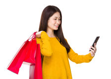 Woman holding shopping bag and using the cellphone Stock Photography
