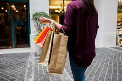 Woman holding shopping bag while walking on vintage street, shop stock photography