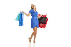 Woman holding shopping bags. Woman in blue dress holding shopping bags Stock Photo
