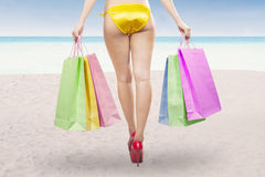 Woman holding shopping bags at beach Stock Photo