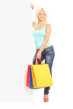 Woman holding shopping bags behind blank panel Stock Photo