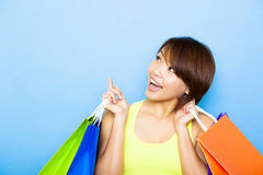 Woman holding shopping bags before blue background Royalty Free Stock Images