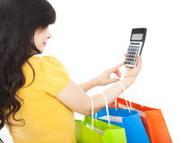 Woman holding shopping bags and calculator Royalty Free Stock Image