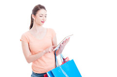 Woman holding shopping bags and checking the tablet Royalty Free Stock Image