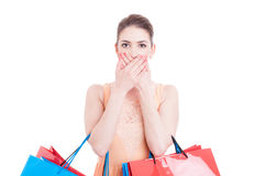 Woman holding shopping bags covering her mouth as being mute Stock Image