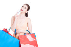 Woman holding shopping bags and credit card acting thoughtful Royalty Free Stock Photos
