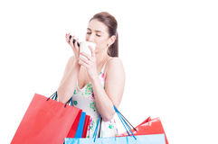 Woman holding shopping bags enjoying a cup of coffee Stock Photography