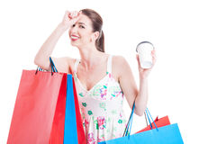 Woman holding shopping bags feeling tired and holding takeaway c Stock Image