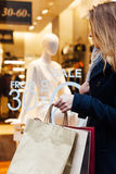 Woman holding shopping bags in front of boutiques Royalty Free Stock Image