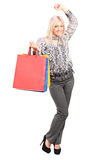 Woman holding shopping bags and gesturing success Royalty Free Stock Images