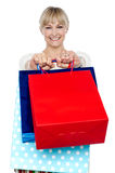 Woman holding shopping bags in her outstretched arms Stock Images
