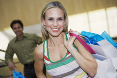 Woman Holding Shopping Bags With Man In Background Stock Photo