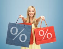 Woman holding shopping bags with percent sign Royalty Free Stock Photo