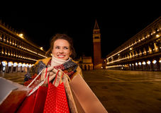 Woman holding shopping bags on Piazza San Marco in evening Stock Photo