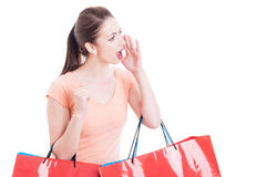 Woman holding shopping bags  shouting or yelling sales concept Stock Images