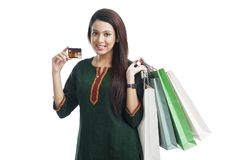 Woman holding shopping bags and showing credit card Stock Image
