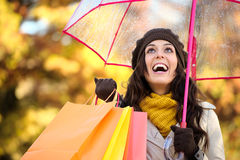 Woman holding shopping bags and umbrella in autumn Royalty Free Stock Photo