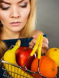 Woman holding shopping basket with fruits inside Stock Photo