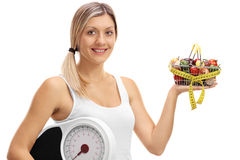 Woman holding a shopping basket and a weight scale Stock Photography