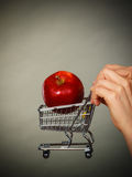 Woman holding shopping cart with apple inside Royalty Free Stock Photography