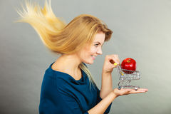 Woman holding shopping cart with apple inside Stock Photo